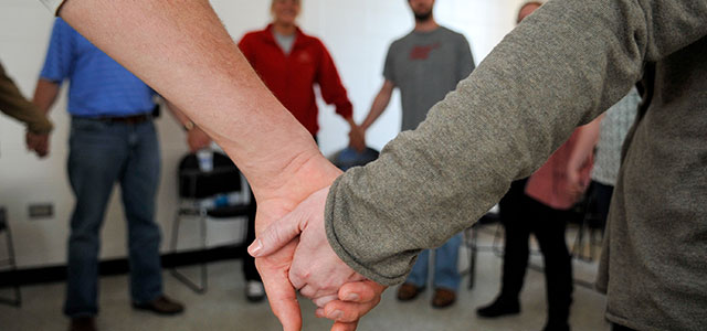 Two people holding hands showing support